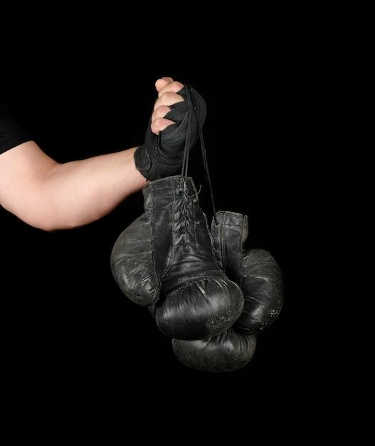 Herenarm omwikkeld met een zwart elastisch sportverband houdt een paar oude vintage leren bokshandschoenen vast Premium Foto