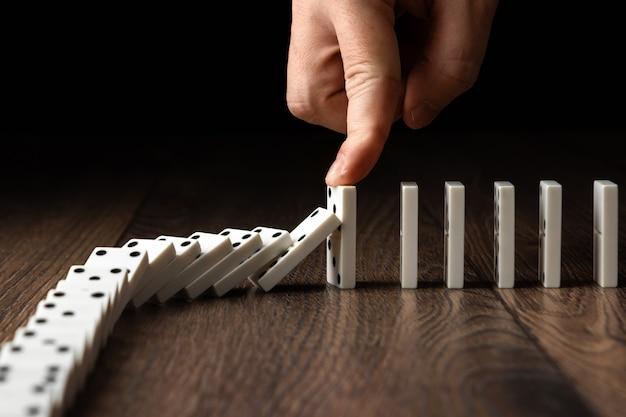 Herenhand gestopt domino-effect Premium Foto