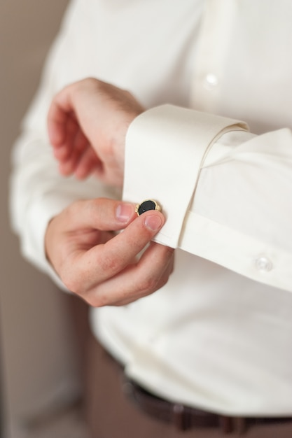 Herenhanden verstellen manchetknopen op de mouwen. Premium Foto