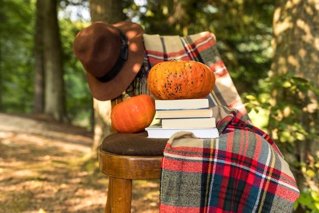 Herfst arrangement met deken en boeken op stoel Gratis Foto