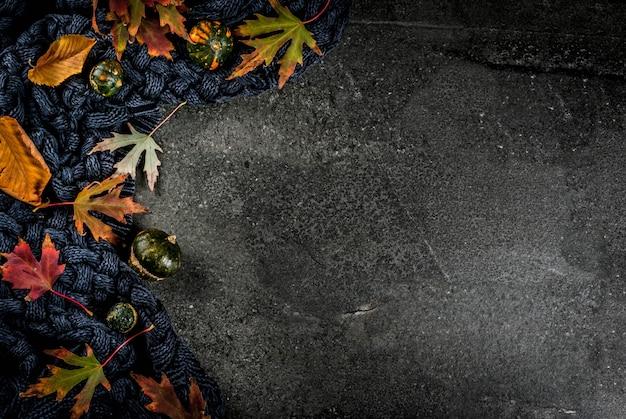 Herfst donkere stenen achtergrond met herfst rode en gele bladeren warme trui of deken en kleine pompoenen, bovenaanzicht kopie ruimte Premium Foto