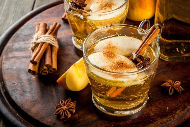 Herfst- en winterdranken. traditionele zelfgemaakte appelcider, cocktail van cider met aromatische kruiden - kaneel en anijs. op een oude houten rustieke tafel, op een dienblad. copyspace Premium Foto