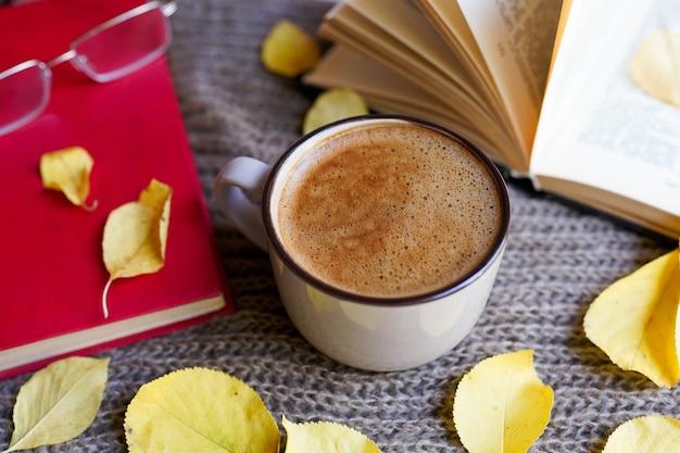 Herfst flatlay met kopje koffie, boeken, glazen, gele bladeren en boeken op sjaal Premium Foto