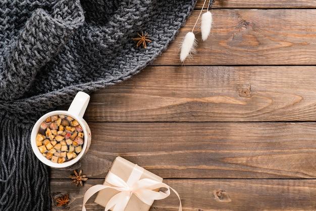 Herfst flatlay samenstelling met kopje kruidenthee, wollen plaid, geschenkdoos en droge bloemen op houten achtergrond Premium Foto