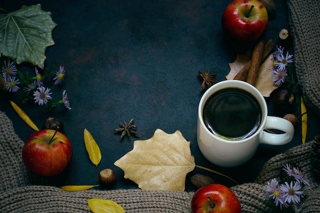 Herfst, herfstbladeren, hete dampende kop koffie en een warme sjaal of vest. seizoensgebonden, ochtendkoffie, zondag ontspannend en stillevenconcept. Gratis Foto