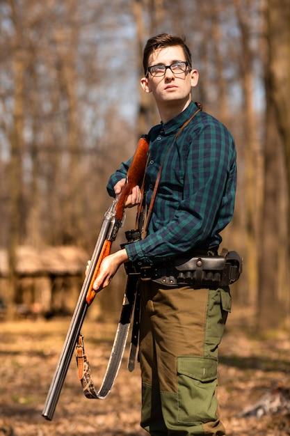 Herfst jachtseizoen. mensenjager met een kanon. jagen in het bos Premium Foto