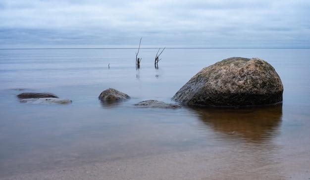 Herfst landschap op het rybinsk reservoir, rusland. een paar rotsen in het water. bewolkte lucht Premium Foto
