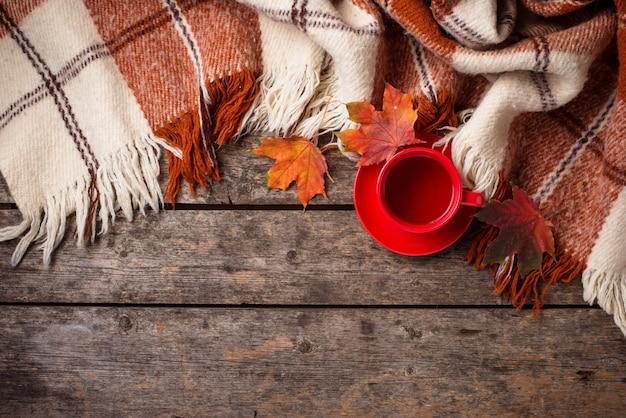 Herfst met kopje thee, plaid en bladeren Premium Foto