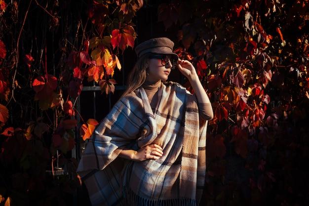 Herfst mode. jonge vrouw die modieuze uitrusting in openlucht draagt Premium Foto