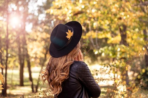 Herfst mode levensstijl concept. mooie jonge europese vrouw met natuurlijk eerlijk haar in een zwarte hoed die in de herfstpark loopt Premium Foto
