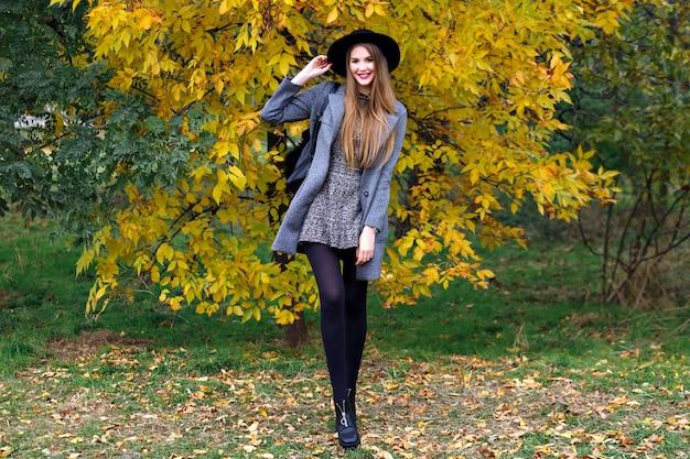 Herfst mode portret van elegante glamour vrouw poseren in verbazingwekkende stadspark, stijlvolle jas, rugzak en vintage hoed. alleen wandelen, koud weer Gratis Foto