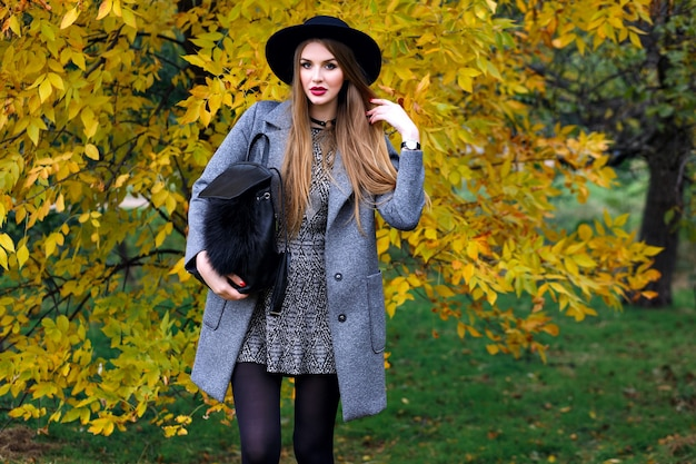 Herfst mode portret van elegante glamour vrouw poseren in verbazingwekkende stadspark, stijlvolle jas, rugzak en vintage hoed. Gratis Foto