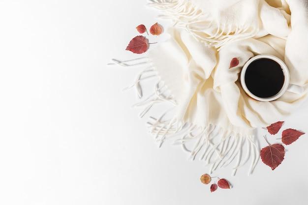 Herfst samenstelling. kop koffie, sjaal en droge bladeren op grijze achtergrond. plat lag, bovenaanzicht, kopie ruimte Premium Foto