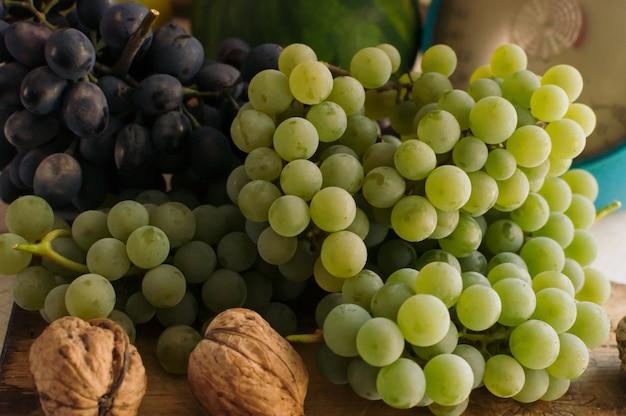 Herfst stilleven met druiven op een houten bord en walnoten rond op een houten witte tafel. op de weegschaal. het concept van de herfstoogst. vrolijke thanksgiving. selectieve aandacht. sjabloon voor ontwerp. Premium Foto