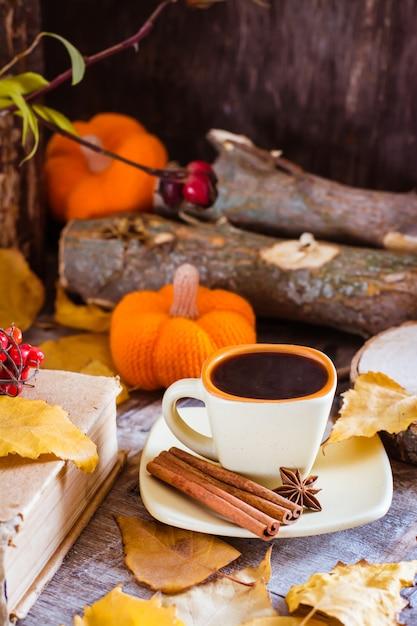 Herfst stilleven met koffie drinken. een kopje zwarte koffie en kaneel op een deel van een boom. Premium Foto