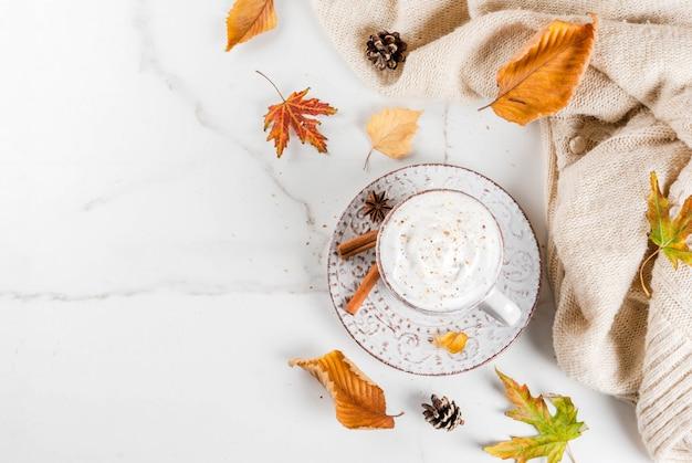 Herfst warme dranken. pompoen latte met slagroom, kaneelanijs op een witte marmeren tafel, met een trui, herfstbladeren en dennenappels. bovenaanzicht Premium Foto