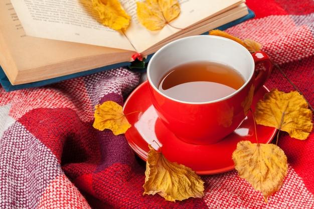 Herfstbladeren, boek en kopje thee Premium Foto