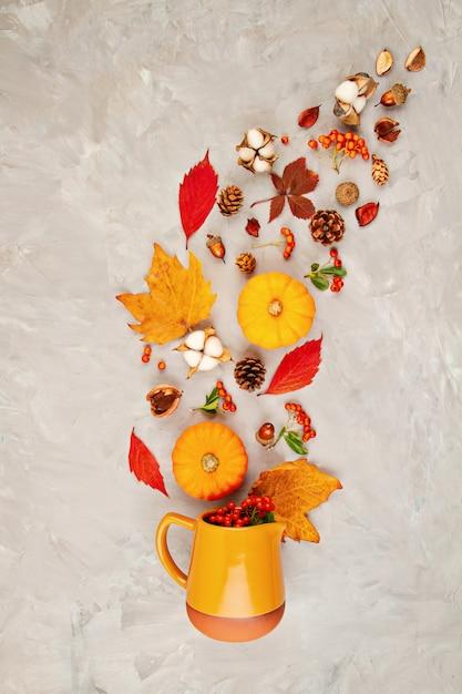 Herfstbladeren, pompoenen, bessen gieten uit een kruik Premium Foto