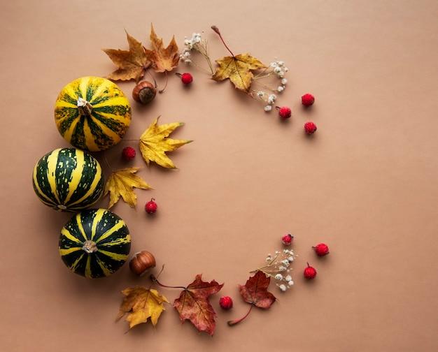 Herfstdecoratie met pompoenen en droge esdoornbladeren in de vorm van een cirkel op een bruine achtergrond Premium Foto