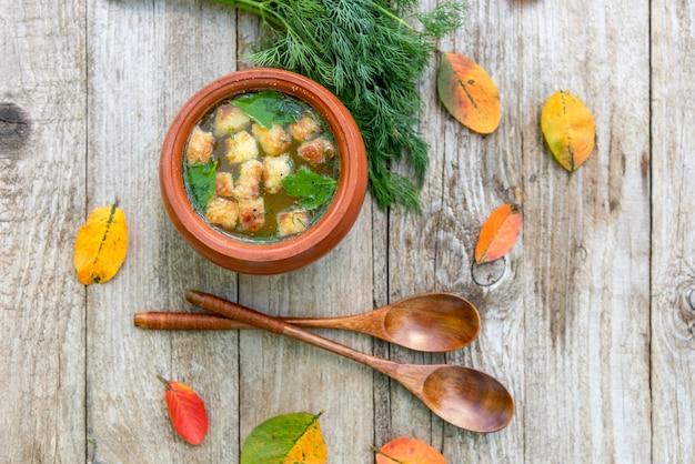 Herfstsoep met crackers in een aarden pot. Premium Foto