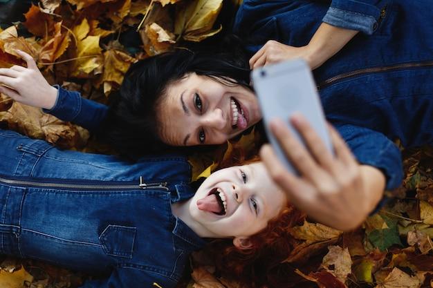 Herfstvibe, familieportret. charmante moeder en haar dochter met rood haar hebben plezier bij het nemen van een selfie op sm Gratis Foto