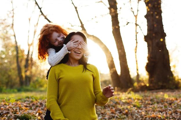 Herfstvibe, familieportret. charmante moeder en haar dochter met rood haar hebben veel plezier op de gevallenen Gratis Foto