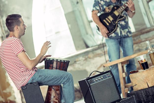Herhaling van rockmuziekband. elektrische gitarist en drummer achter het drumstel. Gratis Foto