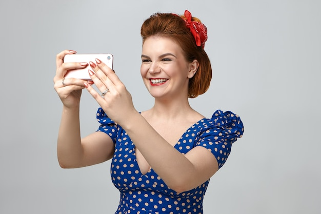 Herinneringen verzamelen. portret van mooie elegante jonge blanke vrouw met rode hoofdband en gestippelde vintage jurk glimlachend vrolijk tijdens het nemen van selfie Gratis Foto
