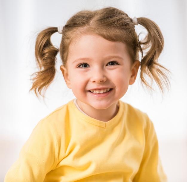 Het aanbiddelijke meisje glimlacht en kijkt Premium Foto