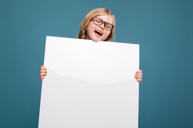 Het aanbiddelijke meisje in roze overhemd, zwarte broeken en glazen houdt lege affiche Premium Foto