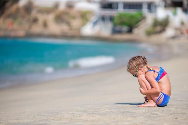 Het aanbiddelijke meisje spelen bij strand tijdens europese vakantie Premium Foto