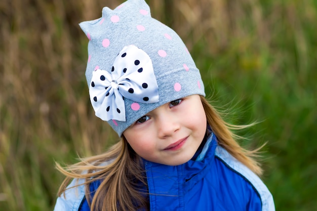 Het aanbiddelijke meisje stellen op vage oppervlakte en binnen het glimlachen aan een camera. winterjas en hoed dragen. mooi jong meisje in de herfst in openlucht. Premium Foto