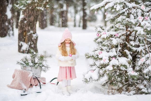 Het aanbiddelijke meisje van het peuter europese kind in hoed en sjaal verfraait kerstmisboom met mooi speelgoed Premium Foto