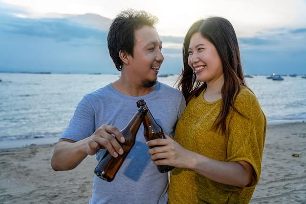 Het aantal aziaten heeft feestdranken met cheer bierflessen op het strand Premium Foto