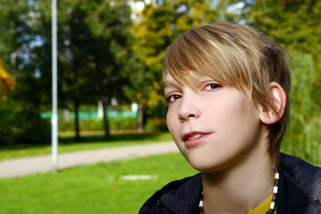 Het aantrekkelijke blondejongen stellen in park Gratis Foto