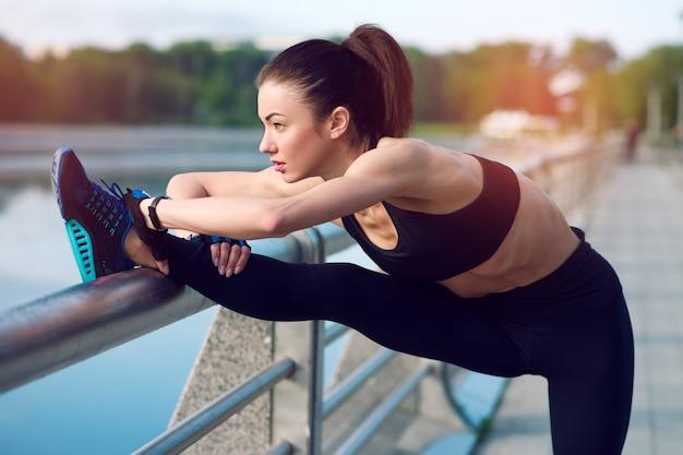 Het aantrekkelijke en sterke vrouw uitrekken zich vóór geschiktheid op het meer in de zomer. sport concept. gezonde levensstijl Premium Foto