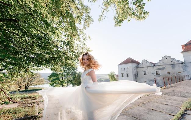 Het aantrekkelijke gelukkige blondemeisje gekleed in witte kleding draait zich om en glimlacht op de zonnige dag dichtbij oud steenkasteel Gratis Foto