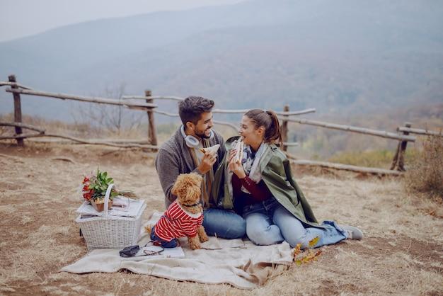 Het aantrekkelijke glimlachende multiculturele paar kleedde toevallige zitting op deken bij picknick en etend sandwiches. hond naar hen te kijken. herfstseizoen. Premium Foto