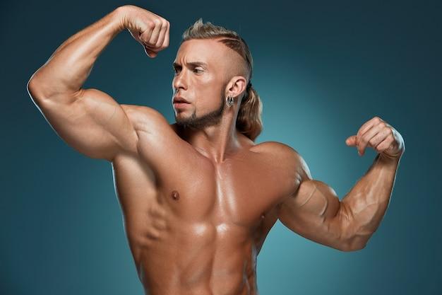 Het aantrekkelijke mannelijke lichaamsbouwer stellen Gratis Foto