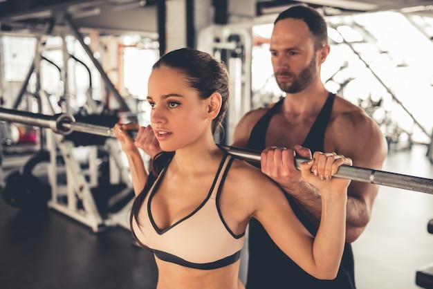 Het aantrekkelijke sportenmeisje werkt met barbell in gymnastiek uit. Premium Foto