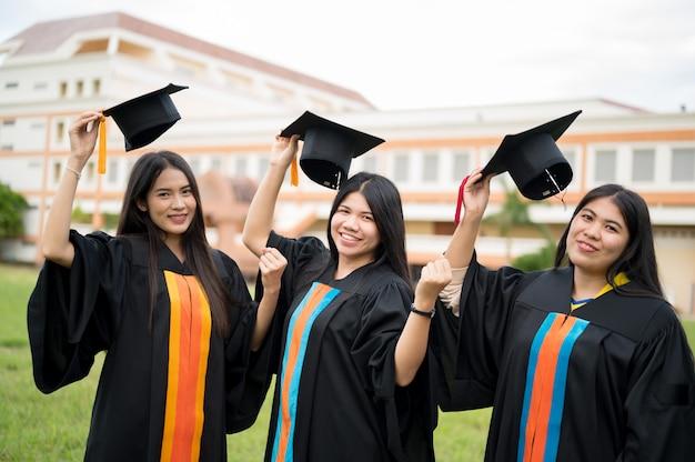 Het achteraanzicht van afgestudeerden dragen zwarte toga's ter voorbereiding op universitaire graden. Premium Foto
