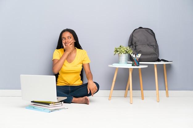 Het afrikaanse amerikaanse meisje van de tienerstudent met lange gevlechte haarzitting op de vloer die een idee denken Premium Foto