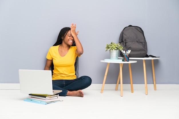 Het afrikaanse amerikaanse meisje van de tienerstudent met lange gevlechte haarzitting op de vloer die twijfels hebben met verwart gezichtsuitdrukking Premium Foto