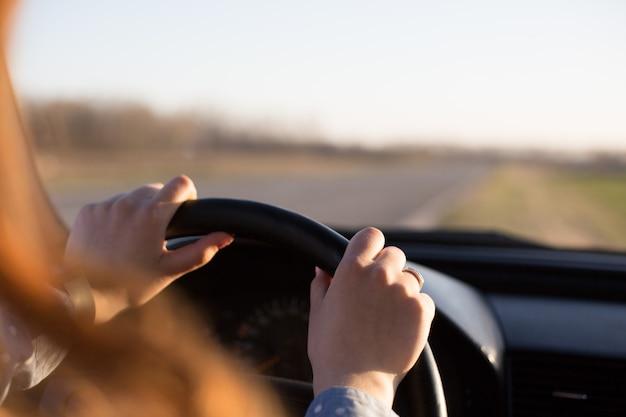 Het anonieme schot van de handen van de jonge vrouw op het stuur tijdens het besturen van de auto, het vrouwtje stopt haar voertuig aan de kant van de weg en geniet van de zonsondergang in haar auto, terwijl ze rust heeft terwijl ze alleen reist. Premium Foto