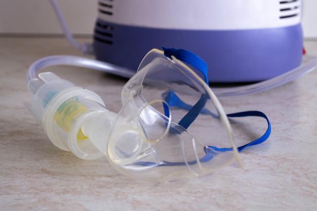 Het apparaat voor het inademen van therapeutische stoom. masker en fles voor medicijnen Premium Foto