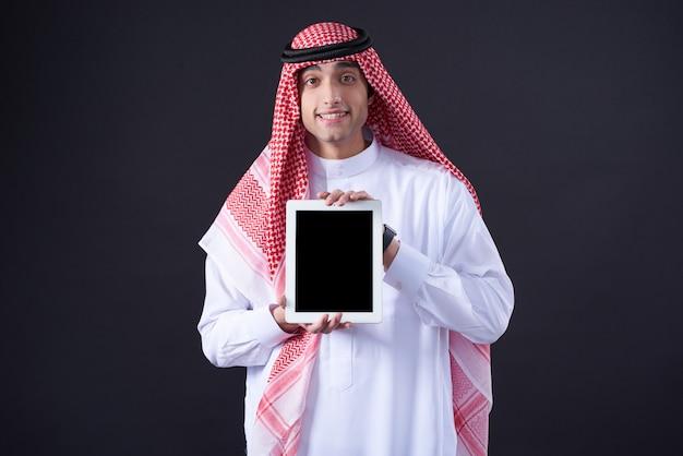 Het arabische mens stellen met zwarte geïsoleerde tablet. Premium Foto