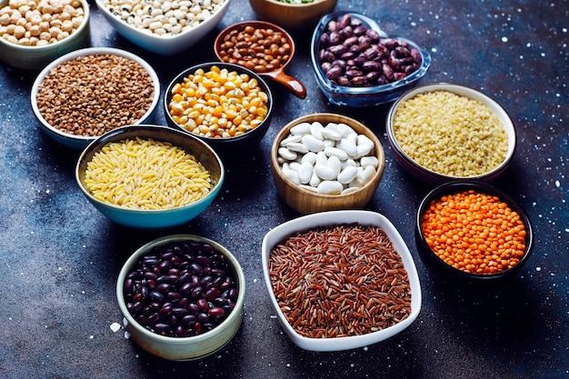Het assortiment van peulvruchten en bonen in verschillende kommen op lichte steenachtergrond. bovenaanzicht. gezond veganistisch eiwitrijk voedsel. Gratis Foto