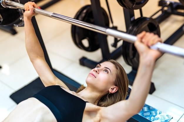 Het atletische meisje heft barbell op liggend op de bank op de simulator in de gymnastiek. Premium Foto