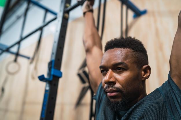 Het atletische mens doen trekt oefening uit bij de gymnastiek. Premium Foto