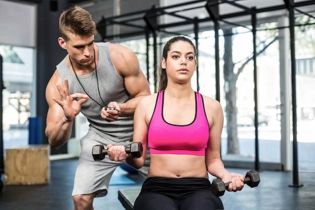 Het atletische vrouw uitwerken geholpen door de trainersmens bij gymnastiek Premium Foto